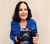 Judy Bailey holding Jim's Polaroid camera