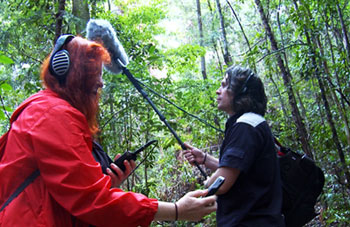 Ros Bandt and Daniel Blinkhorn recording in a lush green landscape during the launch of Biosphere Soundscapes in Noosa Biosphere Reserve.