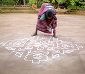 Tamil village elder Renuka 'pouring' a kolam from rice flour, Adishakti, Pondicherry, South India